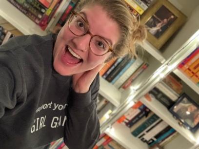 Host Kristen Coates in front of her bookshelf