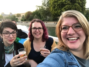 co-hosts Kerry, Rachel, and Kristen offer cheers from a boat in a selfie taken by Kristen